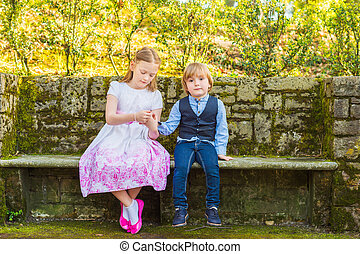 Two cute kids sitting on the bench in a beautiful park, holding hands, wearing celebration clothes