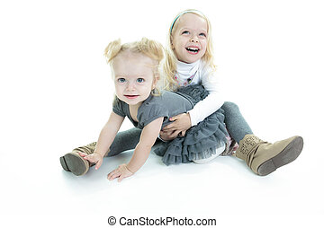 Two cute little blond sisters kneeling on the floor arm in arm c