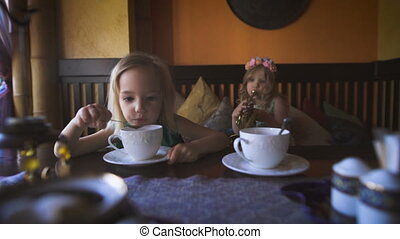 Two cute little blonde girls are having tea in a cafe