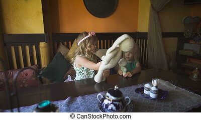 Two cute little blonde girls are playing in a cafe