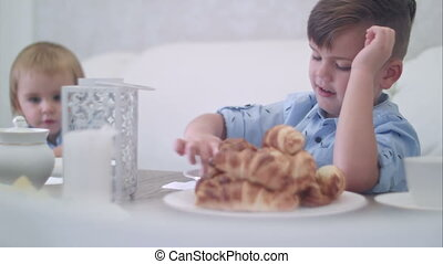 Two cute little boys having fun at the tea table with pastry