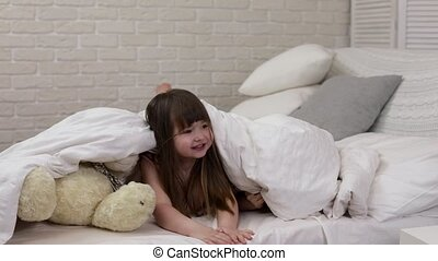 two cute little children girls cover with blanket. Playing...