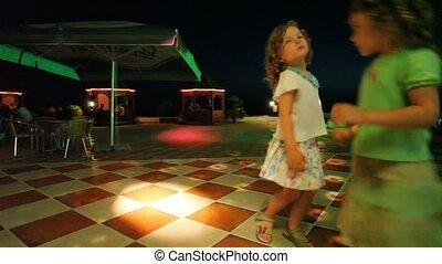 two cute little girls dancing in night club