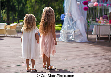 Two cute little girls in beautiful dresses on the wedding ceremony