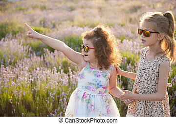 two cute little girls in sunglasses one of them point her finger at something