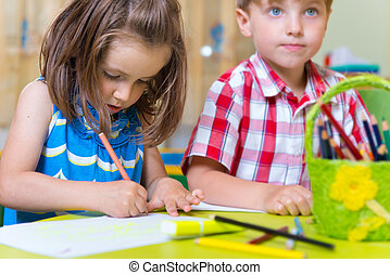 Two cute little preschool kids drawing with crayons at the...