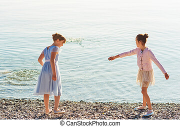 Two cute little preteen girls playing by the lake on a nice sunny day, wearing party dresses