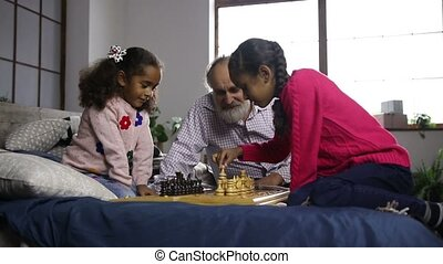 Two cute mixed race sisters playing chess at home