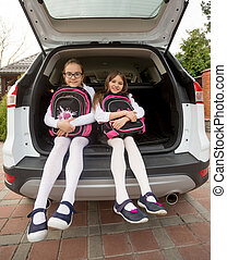 Two cute schoolgirls posing in open car trunk with bags