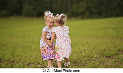 Two cute sisters twins frolicking on a green meadow in summer day. Holding hands smile at each other.