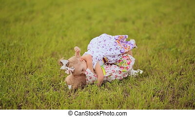 Two cute sisters twins frolicking on a green meadow in summer day. Falling on the grass, laughing and hugging.