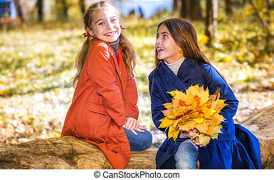 Two cute smiling 8 years old girls chatting in a park on a...