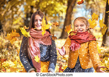 Two cute smiling 8 years old girls playing with leaves in a...