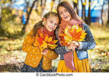 Two cute smiling 8 years old girls posing together in a park...