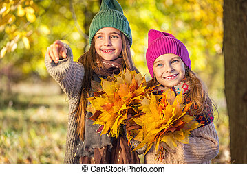 Two cute smiling 8 years old girls walking together in a...