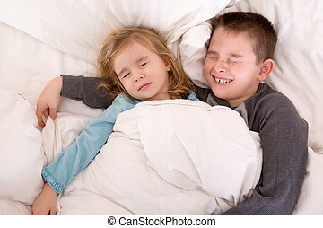 Two cute young children sleeping in bed