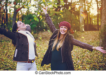 Two cute young woman celebrating autumn