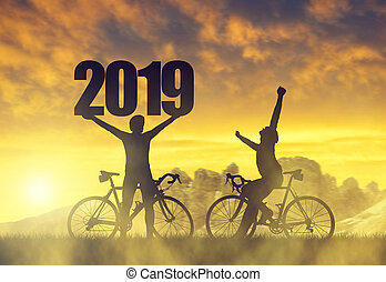 Two cyclist with bicycle at sunset. Forward to the New Year ...