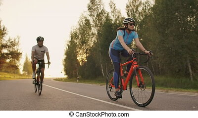 Two cyclists a man and a woman ride on the highway on road bikes wearing helmets and sportswear at sunset in slow motion