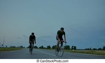 Two cyclists ride on the road in the evening after sunset....