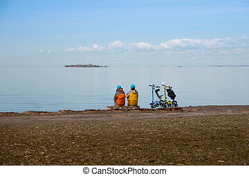 two Cyclists With Bicycles relaxing On Coast And Enjoying View Of Sea. Holiday Travel Activity Concept. road cycling, cycling tour, cycling track, bicycle. Fitness motivation concept. Copy space