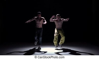 Two dancers performing and dance breakdance on black, shadow, slow motion