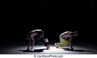 Two dancers performing and start dance breakdance on black, shadow, slow motion