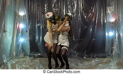 Two dancing women in gas mask
