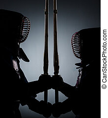 Two dark kendo fighters opposite each other - Two kdark endo...