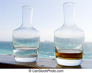 Two decanters with wine on a background of the sea