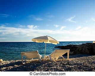 Adriatic beach - Two deck chairs and parasols on the...