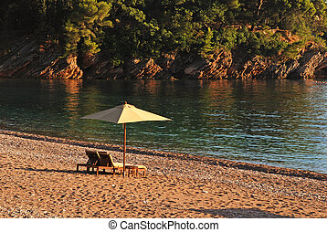 Two deck chairs and umbrella on the beach in rocky bay.