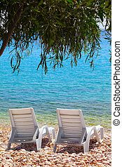 Two deck chairs on beach in sun day