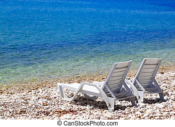 Two deck chairs on beach in sunny summer day