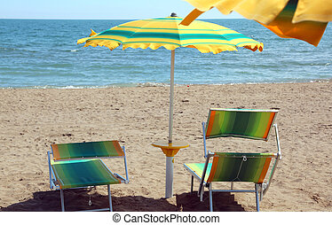 two deckchairs and an umbrella of a resort in front of the sea