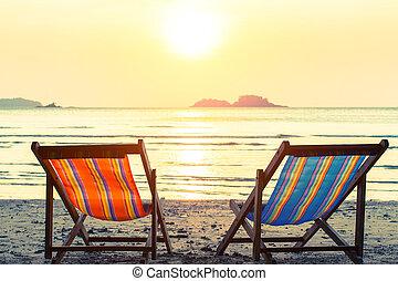 Two deckchairs on a sunny sea beach
