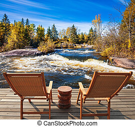 Two deckchairs on the shore of Winnipeg River