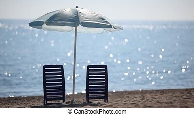 Two deckchairs stand on beach under parasol - Two empty...