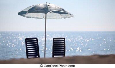 Two deckchairs stand on beach under parasol