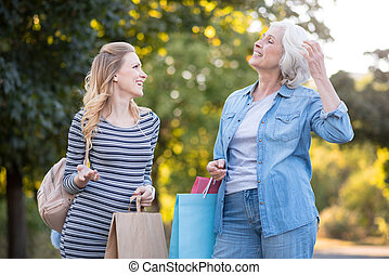 Two delighted pretty woman walking and having conversation.