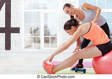 Two delighted women doing stretching in pairs
