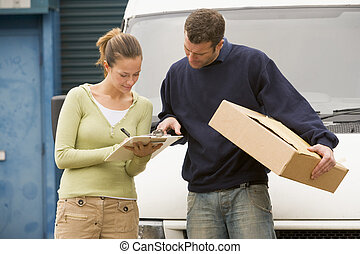 Two deliverypeople standing with van holding clipboard and...