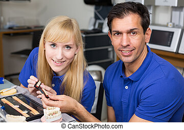 Two dental technicians choosing the right colour from a sample of teeth