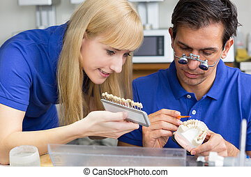 Two dental technicians with colour samples choosing the right colour for dental porcelain