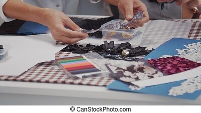 Close up of male and female designers sitting at table with sewing accessories and trying on different variants for new dress. Concept of teamwork and fashion business.