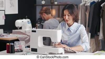 Group of two fashion designers sitting at own workplace and using sewing machine for tailoring clothing. Man and woman creating collection at modern studio.