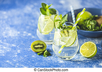 Two detox water or martini tonic cocktail with kiwi, lime, ...