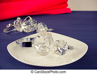 Two diamond rings on the white plate. In the background a bunch of rings.