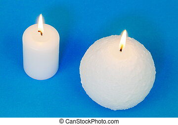 Two different burning candles on blue background