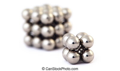 two different cubes assembled from little metallic magnetic balls rotating